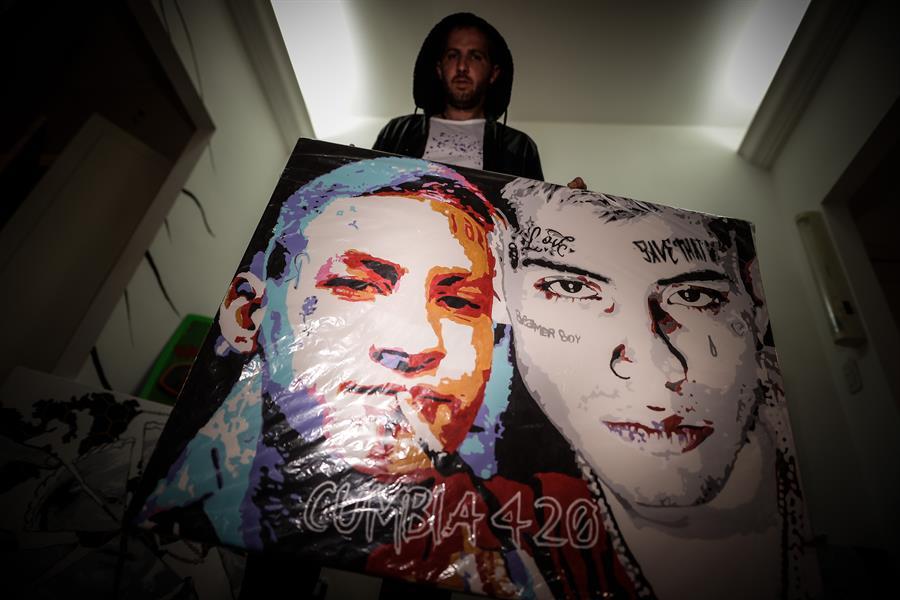 El artista argentino Lukas Nicolino posa junto a sus obras.